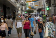People wearing face masks to prevent the spread of coronavirus walk in downtown Madrid, Spain, Wednesday, Sept. 16, 2020. The Spanish capital will introduce selective lockdowns in urban areas where the coronavirus is spreading faster, regional health authorities announced on Tuesday. (AP Photo/Manu Fernandez)