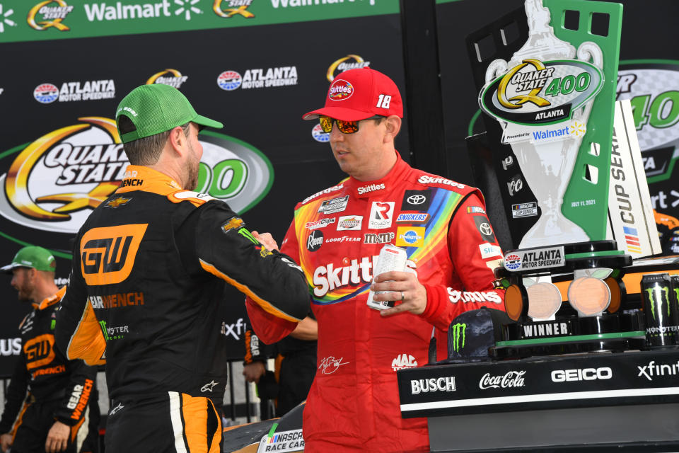Kurt Busch is congratulated by his brother Kyle Busch after winning a NASCAR Cup Series auto race, Sunday, July, 11, 2021, in Hampton, Ga. (AP Photo/John Amis)