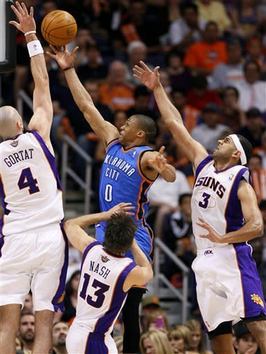 Oklahoma City Thunder guard Russell Westbrook (0) drives between Phoenix Suns' Marcin Gortat (4), of Poland; Steve Nash (13); and Jared Dudley (3) during the second half of an NBA basketball game, Wednesday, April 18, 2012, in Phoenix. (AP Photo/Matt York)