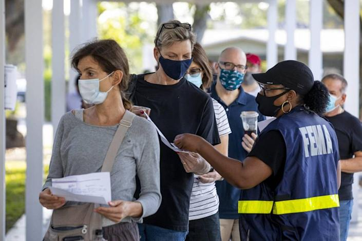 A FEMA employee assists Miami resident Heide Werthamer, 56, while she waits to receive a vaccine at the new FEMA-supported, state-run COVID-19 vaccine satellite site inside the Samuel K. Johnson Youth Center at Charles Hadley Park in Liberty City, Florida, on Friday, March, 19, 2021.