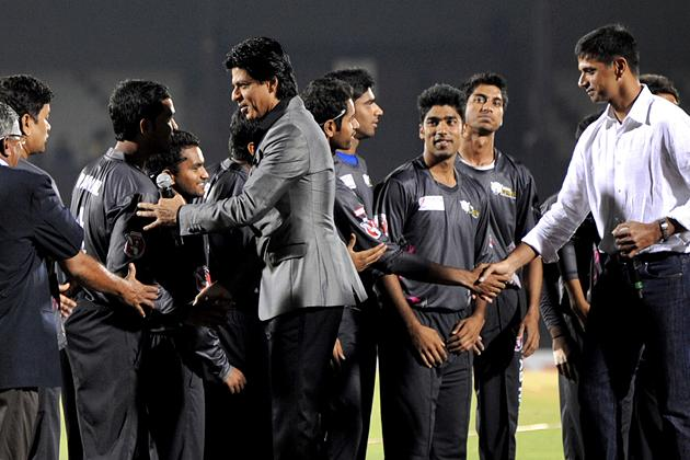 Indian Bollywood actor Shah Rukh Khan (C) and former Indian cricketer Rahul Dravid (R) meet the teams during the grand opening ceremony of the Toyota University Cricket Championship (TUCC) first match of the season in Mumbai on February 23, 2013.  AFP PHOTO        (Photo credit should read STR/AFP/Getty Images)