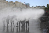 A police water cannon sprays anti-government demonstrators in front of La Moneda presidential palace in Santiago, Chile, Friday, Nov. 1, 2019. Groups of Chileans continued to protests as government and opposition leaders debated the response to nearly two weeks of protests that have paralyzed much of the capital and forced the cancellation of two major international summits. (AP Photo/Rodrigo Abd)
