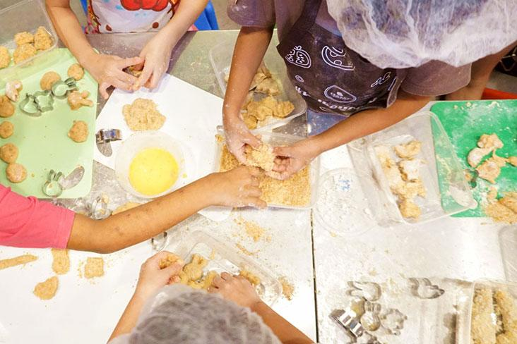 Kids rolling their chicken nuggets in flour during a TedboyCooks class.