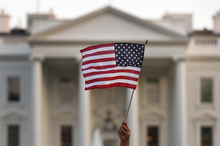 FILE - In this Sept. 2017 file photo, a flag is waved outside the White House, in Washington. The Trump administration announced Friday that it was curbing legal immigration from six additional countries that officials said did not meet security screening standards, as part of an election-year push to further restrict immigration. Officials said immigrants from Kyrgyzstan, Myanmar, Eritrea, Nigeria, Sudan and Tanzania will face new restrictions in obtaining certain visas to come to the United States. But it is not a total travel ban, unlike President Donald Trump's earlier effort that generated outrage around the world for unfairly targeting Muslims. (AP Photo/Carolyn Kaster)