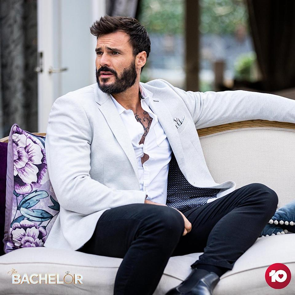 Locky Gilbert on a couch in a suit on The Bachelor