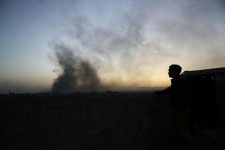 A man watches as smoke rises from Harasta area, as seen from Douma, in the eastern Damascus suburb of Ghouta