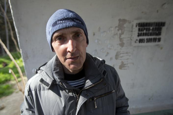 """In this photo taken Tuesday, April 1, 2014, Boris Dashkovsky, a patient of treatment for drug addiction, poses at a bus stop with an advert reading """"Rehabilitation of drug and alcohol addicts"""" in Sevastopol, Crimea. Across the Black Sea peninsula, some 800 heroin addicts and other needle-drug users take part in methadone programs, seen as an important part of efforts to curb HIV infections by taking the patients away from hypodermic needles that can spread the AIDS-causing virus. After Russia's annexation of Crimea methadone was banned. The ban could undermine years of efforts to reduce the spread of AIDS in Crimea. (AP Photo/Pavel Golovkin)"""