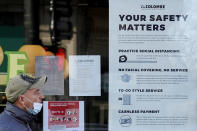 FILE - In this Nov. 12, 2020, file photo, a man walks past a coffee shop as the store displays information signs in Chicago. An increasing number of governors and mayors are imposing restrictions ahead of Thanksgiving for fear that holiday travel and family gatherings will only worsen the record-breaking, coast-to-coast resurgence of the coronavirus. (AP Photo/Nam Y. Huh, File)