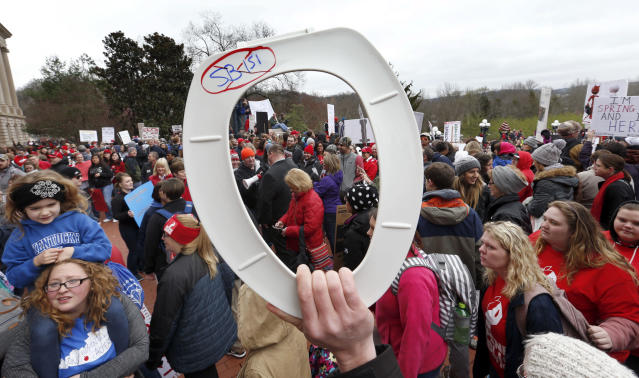 <p>A protester holds a toilet seat as thousands of Kentucky school teachers march Monday morning, April 3, 2018, from the Kentucky Education Association headquarters on Capital Avenue to the State Capitol in Frankfort to protest legislative changes to their pensions and education cuts. (Photo: Charles Bertram/Lexington Herald-Leader via AP) </p>
