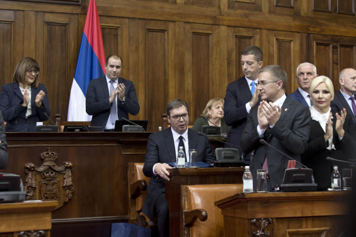 Aleksandar Vucic, the president of Serbia, center, sits as members of the Serbian government and the country's parlamentarians clap during a session of Serbia's parliament in Belgrade, Serbia Monday, May 27, 2019. Vucic addressed the Serb parlamentarians during a session devoted to the situation in Kosovo, which declared independence from Serbia in 2008. (AP Photo/Marko Drobnjakovic)