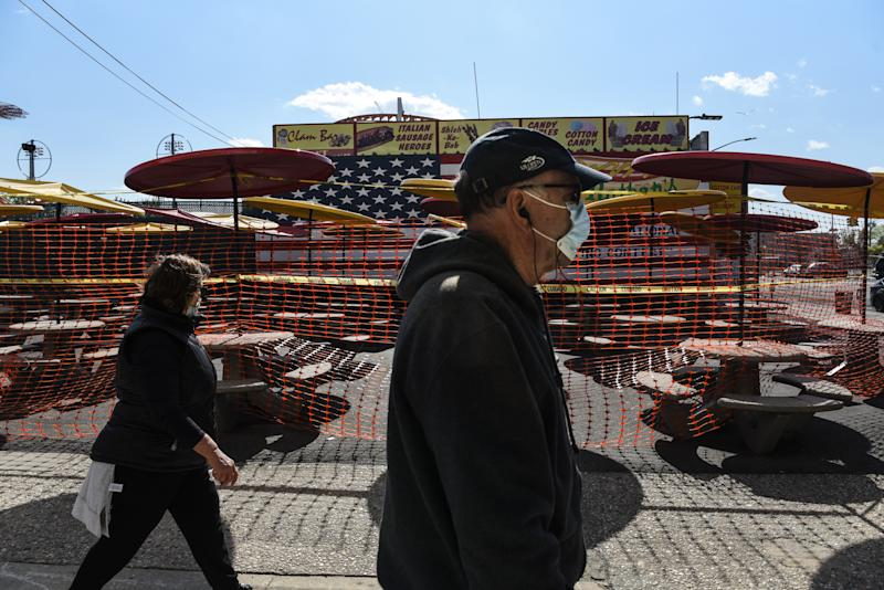 NEW YORK, NY - MAY 13 : People wearing protective masks walk past a closed outdoor seating for Nathan's restaurant on May 13, 2020 in the Coney Island neighborhood in the Brooklyn borough in New York City. New York City is currently in its ninth week of lockdown and governmental guidelines on wearing a mask in public and social distancing are in effect. (Photo by Stephanie Keith/Getty Images)