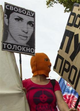 "A woman wearing a trademark Pussy Riot balaclava attends a support rally for the detained members of the Moscow based feminist punk band outside the Russian embassy in Berlin, August 17, 2012. The placard reads: ""Free (Pussy Riot member Nadezhda) Tolokonnikova."""