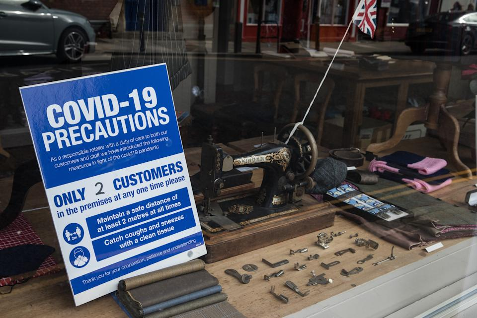 A notice containing COVID-19 precautions is displayed in the window of a tailors shop on 26 September 2020 in Eton, United Kingdom. The Royal Borough of Windsor and Maidenhead is aware of a rise in local coronavirus infections, has a COVID-19 outbreak management plan in place to try to ensure that the numbers do not increase further and has requested access to more coronavirus testing sites with this in mind. (photo by Mark Kerrison/In Pictures via Getty Images)