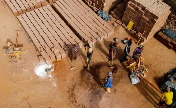 Workers prepare raw soil to make bricks at the Elementerre factory in Mbour