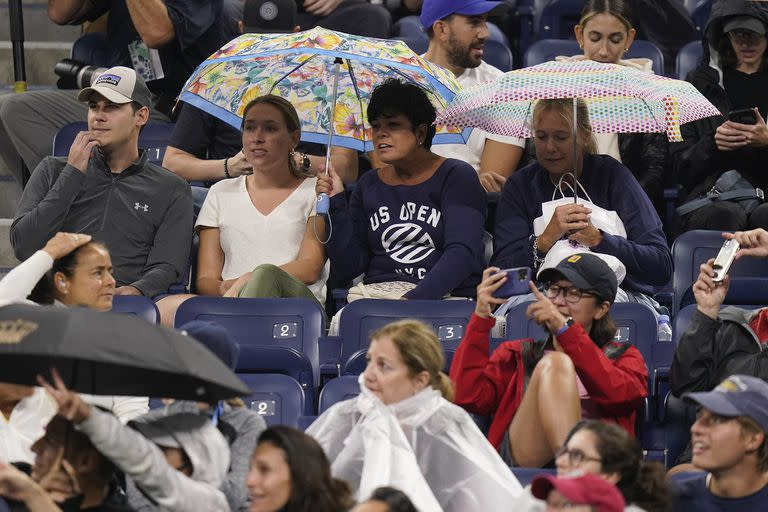 Tennis match in a covered stadium, but with an umbrella