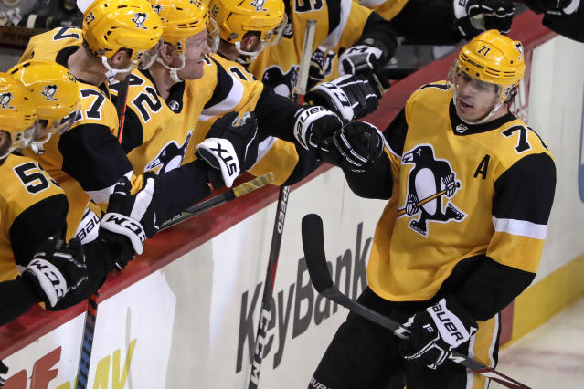 Pittsburgh Penguins' Evgeni Malkin (71) celebrates with teammates after assisting on a goal by Phil Kessel, for the 1,000th point of his NHL career during the third period of an NHL hockey game against the Washington Capitals in Pittsburgh, Tuesday, March 12, 2019. The Penguins won 5-3. (AP Photo/Gene J. Puskar)