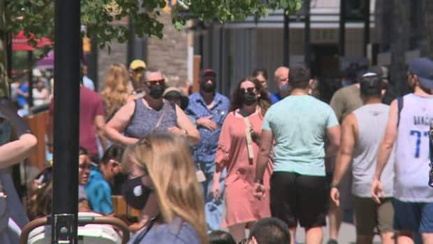 Crowds walking in Banff in June. The town has introduced paid parking for visitors downtown in order to encourage walking and transit.  (Helen Pike/CBC - image credit)