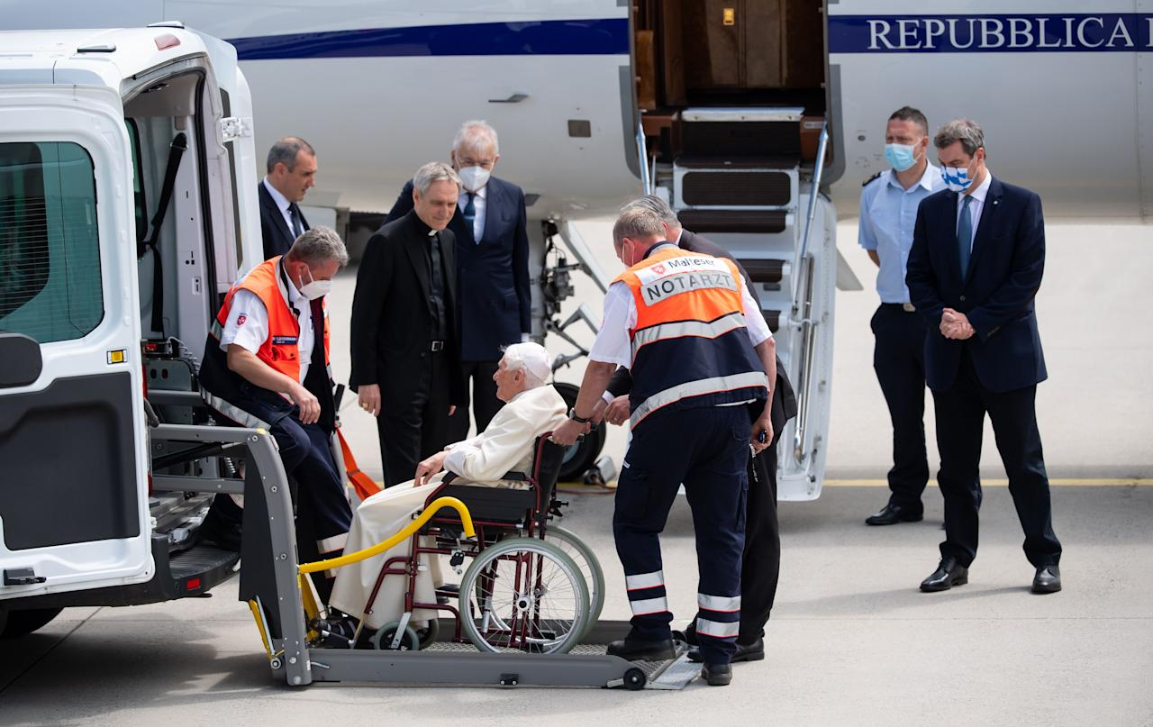 Former pope Benedict XVI (C) sitting in a wheelchair is helped to leave a bus and to get into the plane as his private secretary Georg Gaenswein (3rd L) and Bavaria's State Premier Markus Soeder (R) look on, at the airport in Munich, southern Germany, before the former pope's departure on June 22, 2020. - Former pope Benedict XVI returns to the Vatican from Germany, where he was visiting his sick brother. (Photo by Sven Hoppe / POOL / AFP) (Photo by SVEN HOPPE/POOL/AFP via Getty Images)