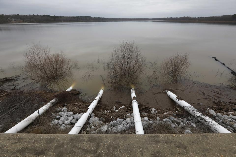 Darkening skies outline the pumps along the Oktibbeha County Lake dam near Starkville, Miss., Wednesday afternoon, Jan. 15, 2020. Officials are hoping the additional drainage will limit the heavy pressure the rain-swollen lake is placing on the dam. County officials believe a breach would affect an estimated 130 properties and several highways. (AP Photo/Rogelio V. Solis)