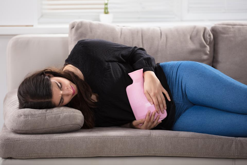 Young Woman Lying On Couch Holding Pink Hot Water Bag On Stomach At Home