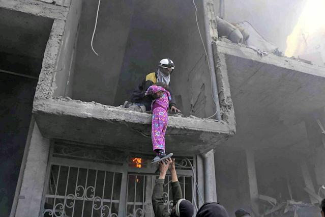 <p>A member of the Syrian Civil Defense group rescues a young girl from a building damaged by airstrikes and shelling by Syrian government forces, in Ghouta, a suburb of Damascus, Syria on Feb. 21, 2018. (Photo: Syrian Civil Defense White Helmets via AP) </p>