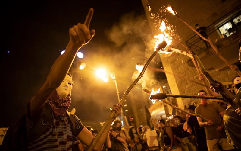 Protesters light torches during a protest against Israel's Prime Minister Benjamin Netanyahu outside his residence in Jerusalem - AP Photo/Oded Balilty
