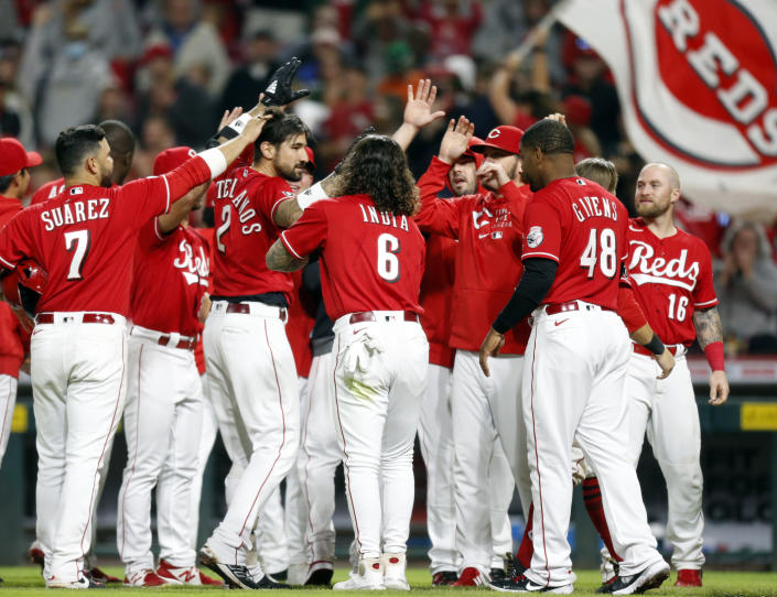 Cincinnati Reds' Nick Castellanos (2) celebrates with his teammates after hitting a home run against Washington Nationals pitcher Patrick Murphy to win the game during the ninth inning of a baseball game in Cincinnati Saturday, Sept. 25, 2021. The Reds won 7-6. (AP Photo/Paul Vernon)