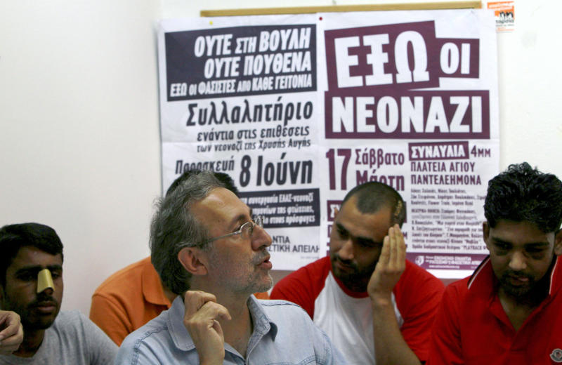 """United Against Racism and Fascist Violence Movement coordinator Petros Constantinou, center, talks to the media as immigrants are seen in the background at United Against Racism and Fascist Violence Movement office during a press conference in Athens, Thursday, June 21, 2012. An immigrants support group is accusing an extreme right wing group of launching a wave of attacks against immigrants prior last weekend's crucial elections in Greece and in the days following the poll. United Against Racism and Fascist Violence Movement coordinator Petros Constantinou said there have been """"hundreds"""" of such attacks and accused the Golden Dawn party of organizing the violence. Constantinou said Golden Dawn's strong showing in the elections in which they won 18 seats after campaigning on an anti-immigrant and anti-bailout platform has emboldened the group to step up such attacks. (AP Photo/Petros Karadjias)"""