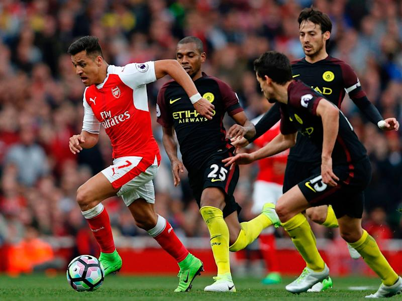 Alexis Sanchez carries the ball forward past Manchester City's midfield: Getty