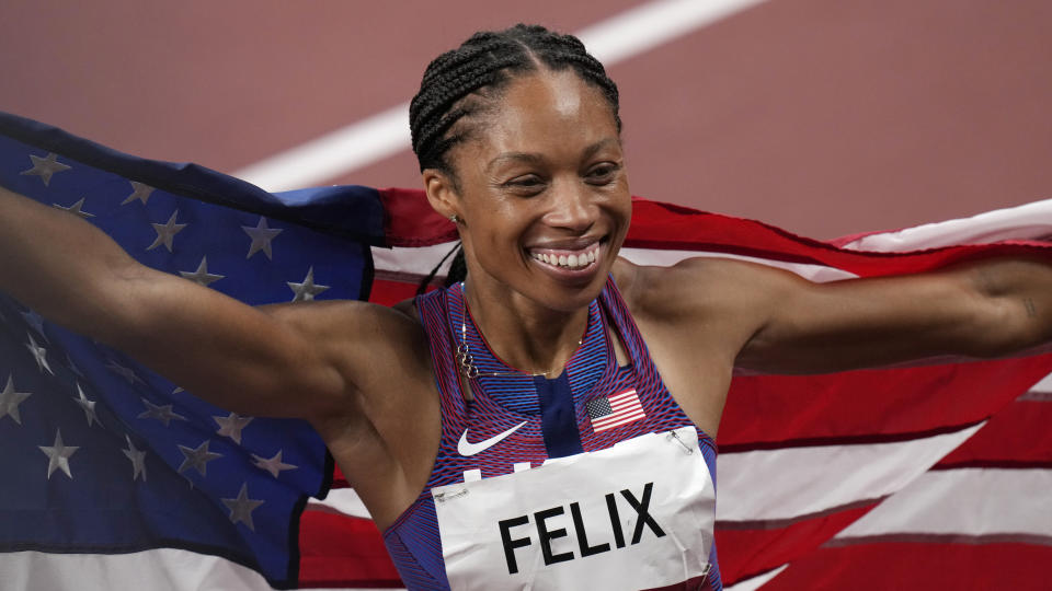 Allyson Felix smiles while holding an American flag on a track after winning a bronze medal.
