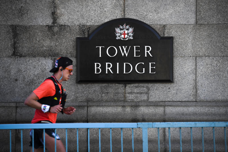 A runner is seen on Tower Bridge on the day that would have been the London Marathon, which has been postponed due to the coronavirus outbreak, in London, Sunday, April 26, 2020.(AP Photo/Alberto Pezzali)