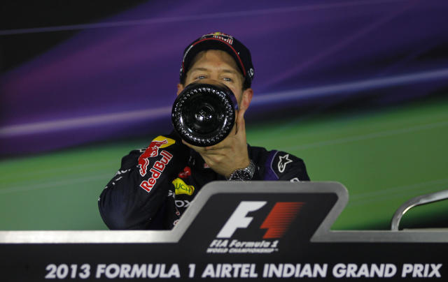 Red Bull driver Sebastian Vettel drinks champagne during a press conference after winning the Indian Formula One Grand Prix and his 4th straight F1 world drivers championship at the Buddh International Circuit in Noida, India, Sunday, Oct. 27, 2013. (AP Photo/Altaf Qadri)