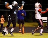 Panther Creek's Khilen Holliman (11) celebrates the tying touchdown ahead of Olympic's Damian Payton (23) in the fourth quarter. The Olympic Trojans and the Panther Creek Catamounts met in a NCHSAA playoff game in Cary, N.C. on April 16, 2021.