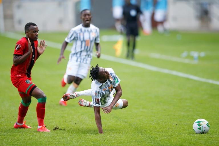 Christian Kouame (R) of the Ivory Coast is fouled by Charles Petro (L) of Malawi during a World Cup qualifier in Soweto, South Africa, on Friday. (AFP/Phill Magakoe)