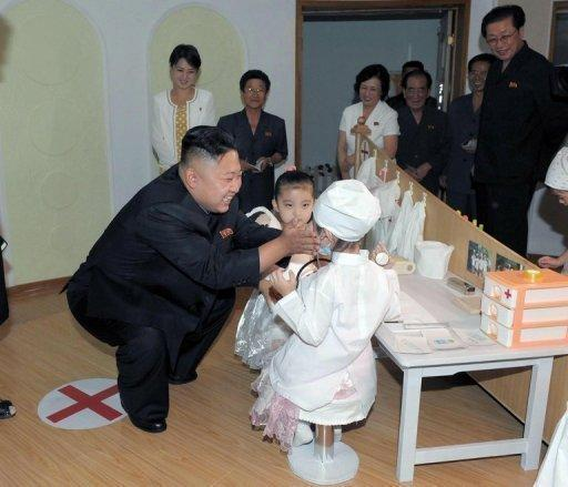 North Korean leader Kim Jong-Un talks to two children during a visit to the Kyongsang kindergarten in Pyongyang on July 15. Kim was accompanied by a woman believed to be Ri Sol-Ju (wearing yellow polka dot dress)