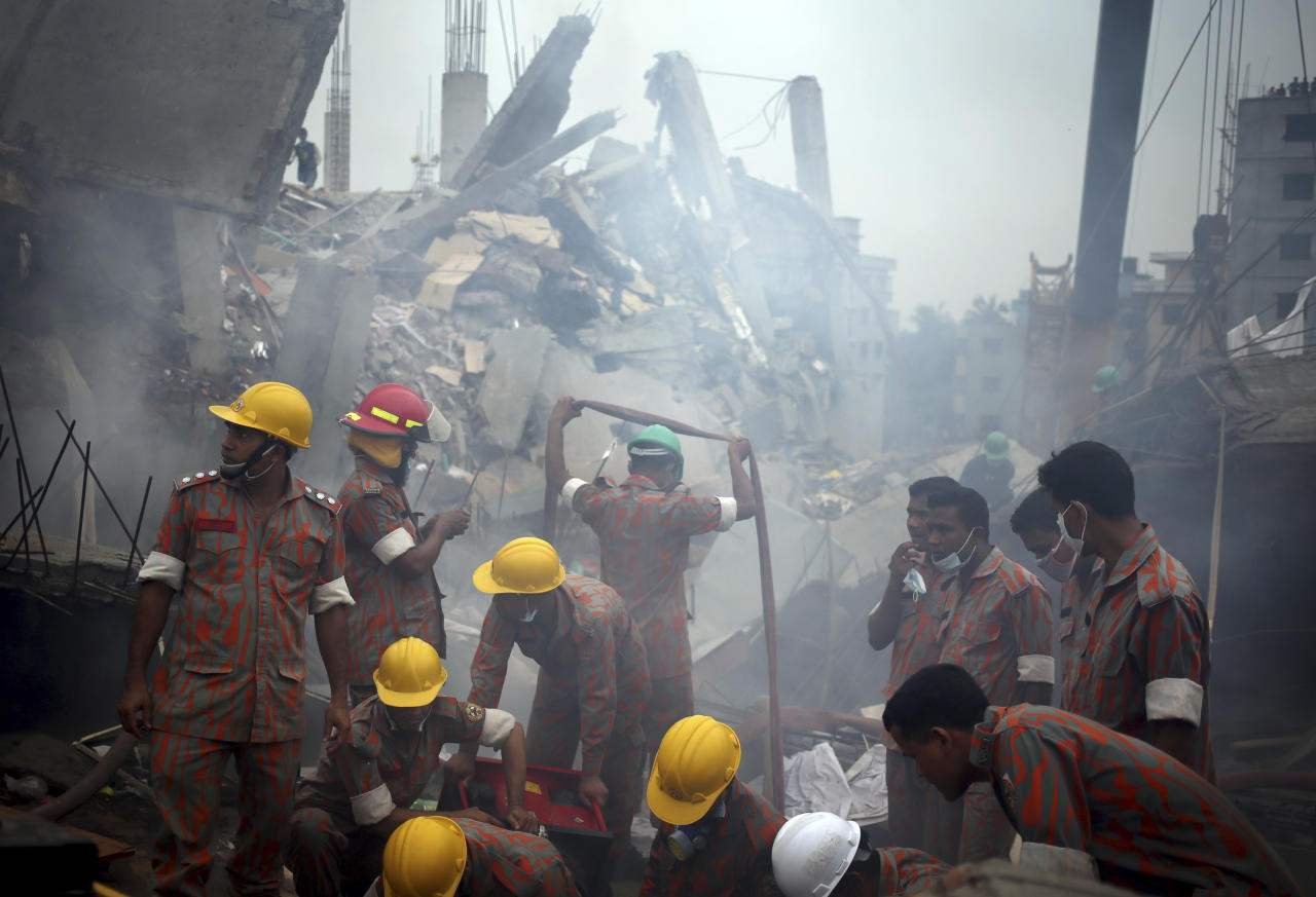 Workers and fire fighters are shrouded in smoke as they prepare to dislodge the debris and fallen ceiling of the garment factory building which collapsed in Savar, near Dhaka, Bangladesh on Monday, April 29, 2013. Rescue workers in Bangladesh gave up hopes of finding any more survivors in the remains of a building that collapsed five days ago, and began using heavy machinery on Monday to dislodge the rubble and look for bodies - mostly of workers in garment factories there. At least 381 people were killed when the illegally constructed, 8-story Rana Plaza collapsed in a heap on Wednesday morning along with thousands of workers in the five garment factories in the building.(AP Photo/Wong Maye-E)