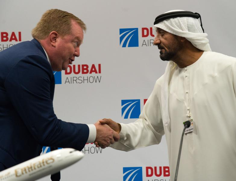 Boeing Commercial Airplanes president and CEO Stanley A. Deal, left, shakes hands with Sheikh Ahmed bin Saeed Al Maktoum, the chairman and CEO of the Dubai-based long-haul carrier Emirates, at the Dubai Airshow in Dubai, United Arab Emirates, Wednesday, Nov. 20, 2019. Dubai's carrier Emirates announced Wednesday a firm order for 30 Boeing 787 Dreamliners in deal valued at $8.8 billion. (AP Photo/Jon Gambrell)