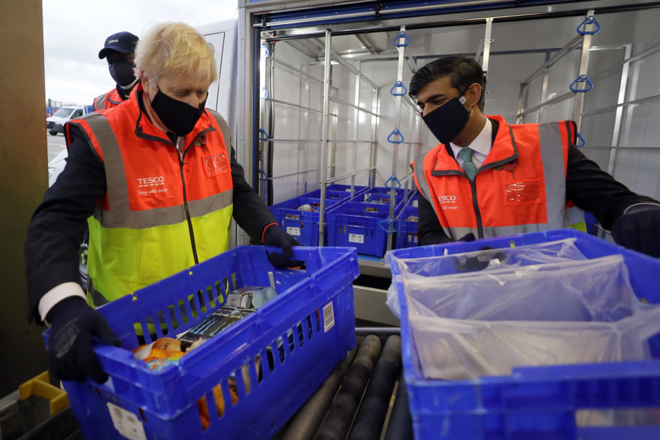 Britain's Prime Minister Boris Johnson and Chancellor Rishi Sunak load a delivery van with baskets of shopping during a visit to a tesco.com distribution centre in London, Wednesday, Nov. 11, 2020. (AP Photo/Kirsty Wigglesworth, pool)