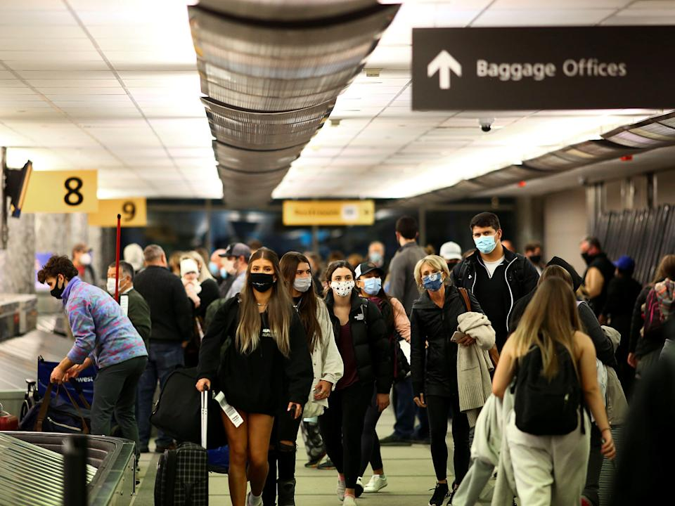 FILE PHOTO: Travelers wearing protective face masks to prevent the spread of the coronavirus disease (COVID-19) reclaim their luggage at the airport in Denver, Colorado, U.S., November 24, 2020.