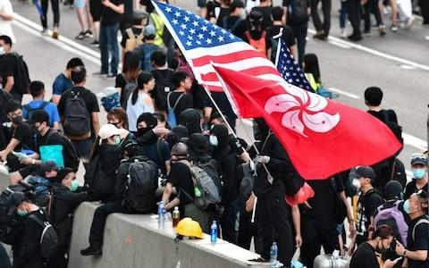 A man waves a US and Hong Kong flag while standing on a divider after he and other protesters occupied Harcourt Road while marching against a controversial extradition bill in Hong Kong on July 21, 2019. - Credit: afp