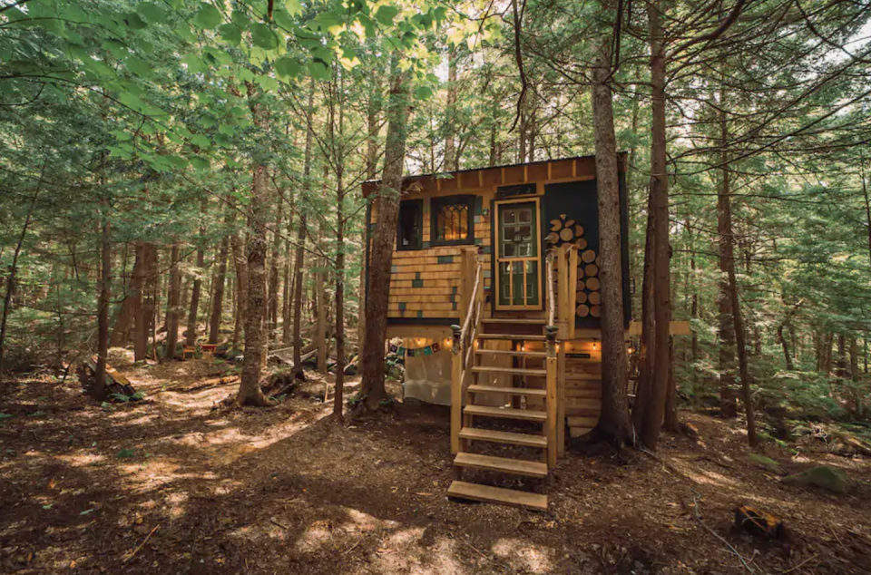 """<p><strong><a href=""""https://www.airbnb.com/rooms/27627590"""" rel=""""nofollow noopener"""" target=""""_blank"""" data-ylk=""""slk:Treehouse In The Woods:"""" class=""""link rapid-noclick-resp"""">Treehouse In The Woods:</a> Hardwick, Vermont</strong></p><p>This tiny little treehouse in the woods is located only a few feet away from a bubbling stream that really adds to the peacefulness of the spot. The inside is furnished so beautifully that you'll forget you're in a treehouse, and string lights along the outside and hanging off the deck make this space even more charming. There's a limited water system, a composting toilet, and space to hang out outside. It's also on the same property as a main house, where a real bathroom awaits if needed. </p>"""