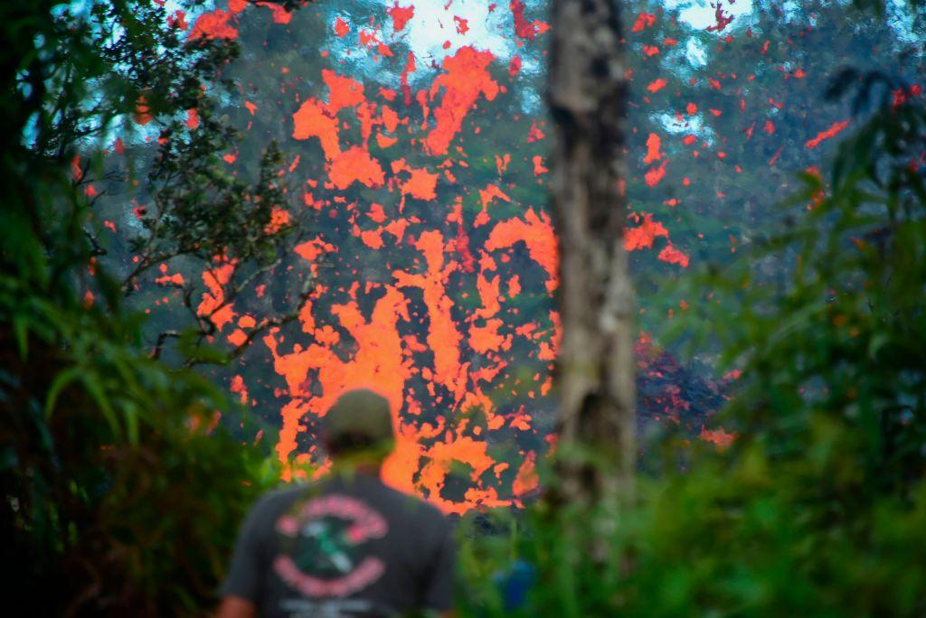 <p>A man watches as lava is seen coming from a fissure in Leilani Estates subdivision on Hawaii's Big Island on May 4, 2018. Up to 10,000 people have been asked to leave their homes on Hawaii's Big Island following the eruption of the Kilauea volcano that came after a series of recent earthquakes. (Photo from Frederic J. Brown/AFP/Getty Images) </p>