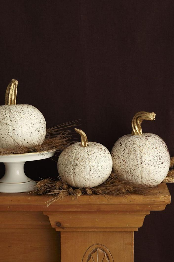 <p>Flick a paint brush covered in gold acrylic paint onto a few white pumpkins — and paint the stems gold too, for an extra sparkling touch. </p>
