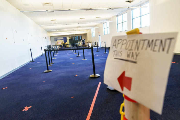 A sign points the way to a check-in area at a coronavirus mass-vaccination site at the former Citizens Bank headquarters in Cranston, R.I., Thursday, June 10, 2021. The U.S. is confronted with an ever-growing surplus of COVID-19 vaccines, looming expiration dates and stubbornly lagging demand at a time when the developing world is clamoring for doses to stem a rise in infections. (AP Photo/David Goldman)