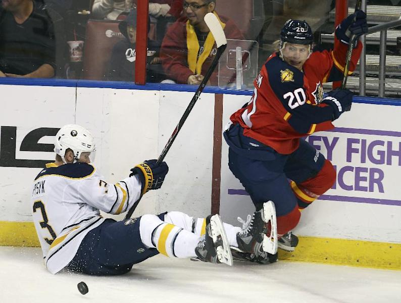 After knocking Buffalo Sabres' Mark Pysyk (3) to the ice, Florida Panthers' Sean Bergenehim chases the puck during the second period of an NHL hockey game in Sunrise, Fla., Friday, Oct. 25, 2013. (AP Photo/J Pat Carter)