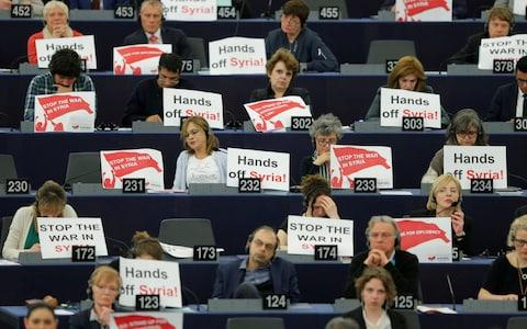 "Members of the European Parliament hold placards saying ""Stop the War in Syria"" before a debate on the Future of Europe  - Credit: VINCENT KESSLER/REUTERS"