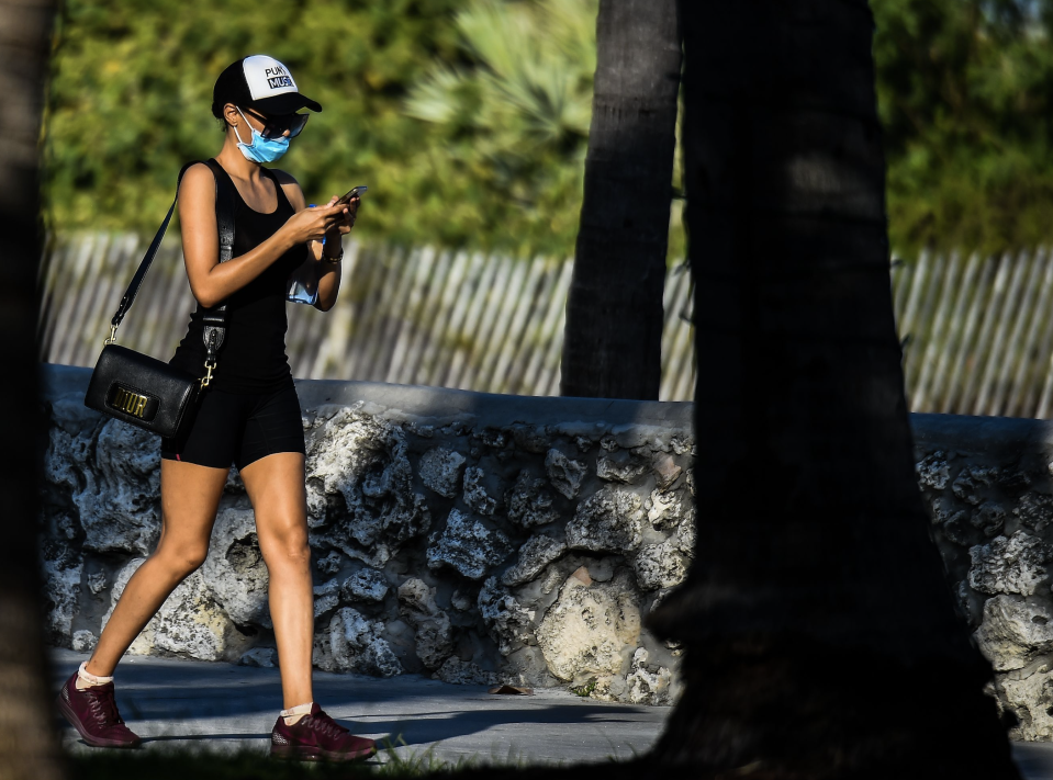 A woman wears a mask as she walks on Ocean Drive in South Beach, Miami, amid fears over the spread of the novel coronavirus (COVID-19) on March 31, 2020. (Photo: CHANDAN KHANNA / AFP) (Photo by CHANDAN KHANNA/AFP via Getty Images)