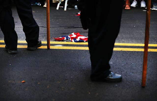 <p>KNA torn up confederate flag lays on the ground beside police as supporters for and against a Fort Sanders Confederate memorial monument face off in Aug. 26, 2017 in Knoxville, Tenn. (Photo: Spencer Platt/Getty Images) </p>