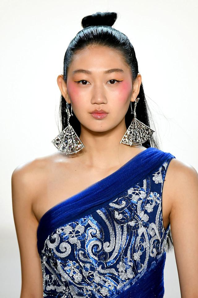 """<p><strong>THE LOOK: </strong>Cherry blossom cheeks and lips. Makeup artist Daniel Martin swept shades of pink from the eyes to the temples. He defined the eyes with winged black liquid eyeliner and a pop of yellow on the outer corners. A swipe of cherry lip gloss rounded out the look. </p> <p><strong>KEY PRODUCTS: </strong><a href=""""https://www.orcecosmetics.com/blogs/come-closer-skin-perfecting-foundation/our-commitment"""" target=""""_blank"""">Orcé Come Closer Foundation</a> and <a href=""""https://www.honestbeauty.com/products/liquideyeliner"""" target=""""_blank"""">Honest Beauty Liquid Eyeliner</a>. </p>"""