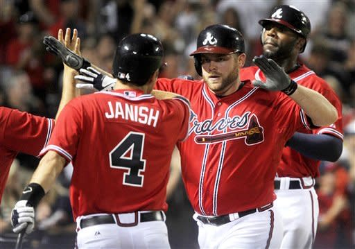 Atlanta Braves' Brian McCann, second from right, celebrates his two-run homer with Paul Janish (4) as he and Jason Heyward approach the dugout during the fifth inning of a baseball game against the Philadelphia Phillies, Friday, July, 27, 2012, in Atlanta. (AP Photo/John Amis)